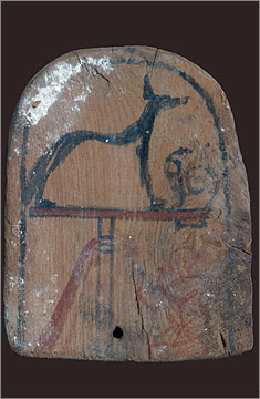 Wooden top to a police standard depicting a figure kneeling beneath an image of the god Wepwawet on a stand. Found in the Sanctuary of the Main Chapel.