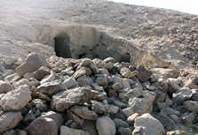 An Amarna Period rock-cut tomb at the far end of the wadi. The dry stone walls surrounding the mouth of the tomb are from its reuse in Late Antique times.