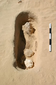 Figure 18. Burial pit <12093> after excavation of unit (12094), showing limestone boulders and fragments of timber resting on top of unit (12102). View site north-west.