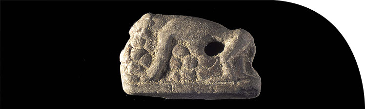 Limestone figurine of a monkey straddling a heap of fruit (object no. 34119, Grid 12).