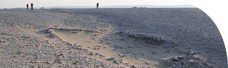 The desert above the Stone Village, a small stone hut in the foreground.